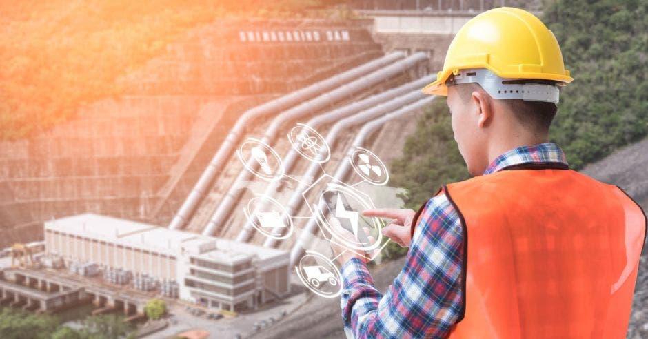 un hombre con caso amarillo mira desde lo alto de una planta de electricidad. Concepto de energía renovable