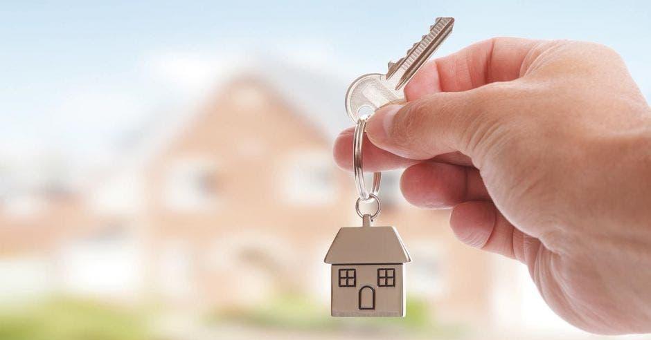 Persona sostiene en sus manos llaves con llavero  de casa