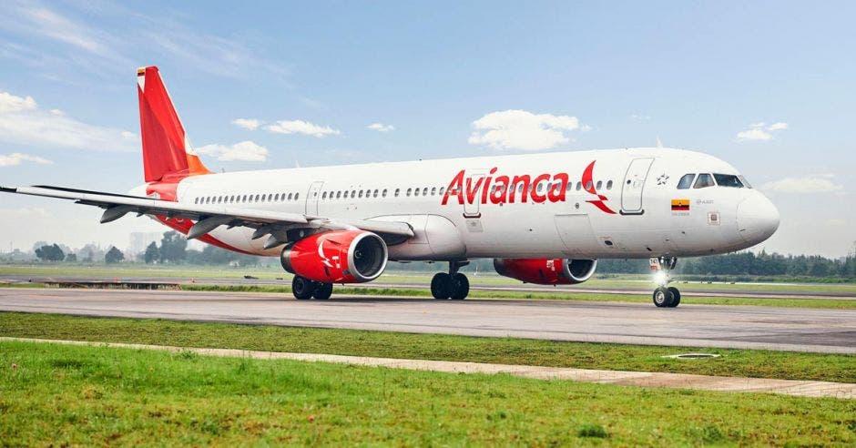 un avión blanco y rojo sobre una pista de aterrizaje
