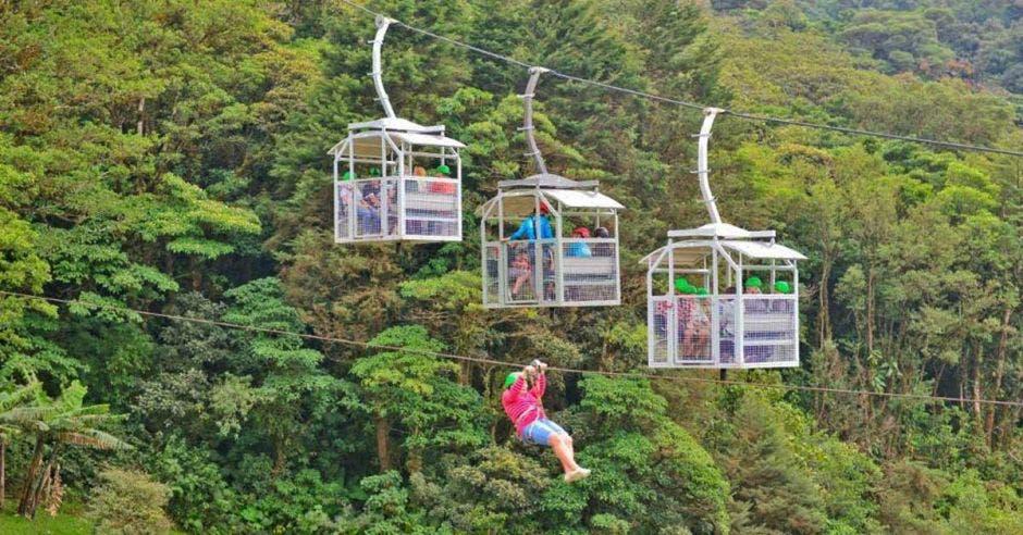un grupo de turistas sube en teleférico por el bosque tropical