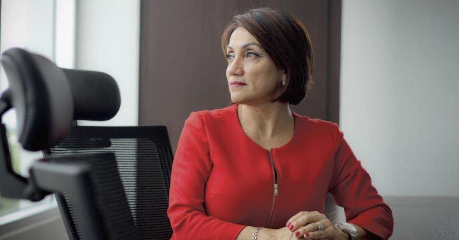 una mujer de traje rojo sentada en una oficina