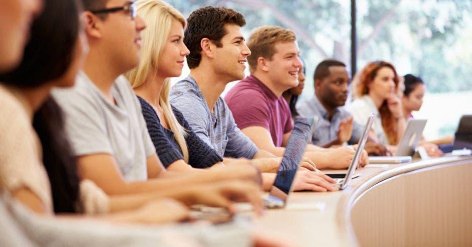 Jóvenes prestando atención al profesor en auditorio