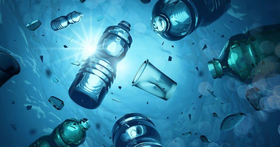 Botellas plásticas problemáticas y microplásticos flotando en el océano abierto. Concepto de contaminación de plástico marino