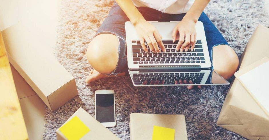 una mujer usando una computadora en la sala de su casa. Concepto de emprendedora.
