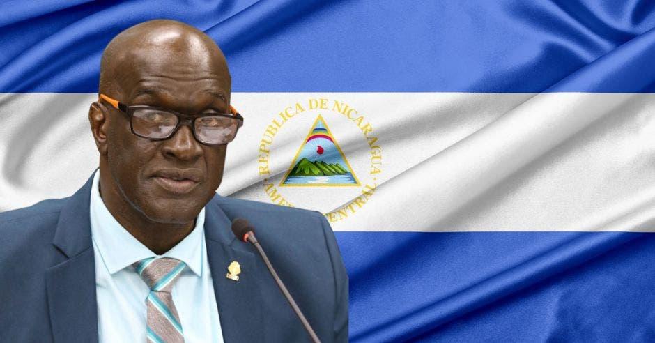 un hombre de traje y corbata sobre la bandera de nicaragua