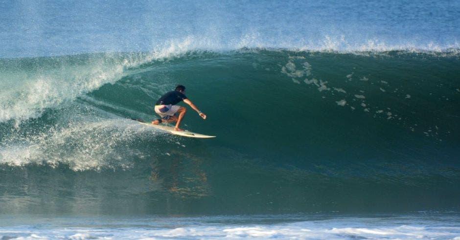 un hombre de camisa azul surfeando