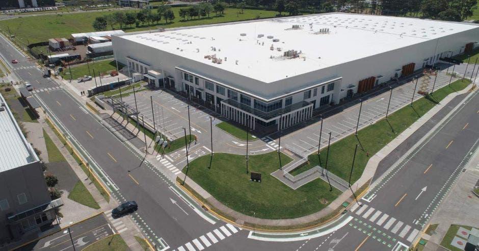 un edificio gris de grandes dimensiones con un amplio parqueo y zona verde