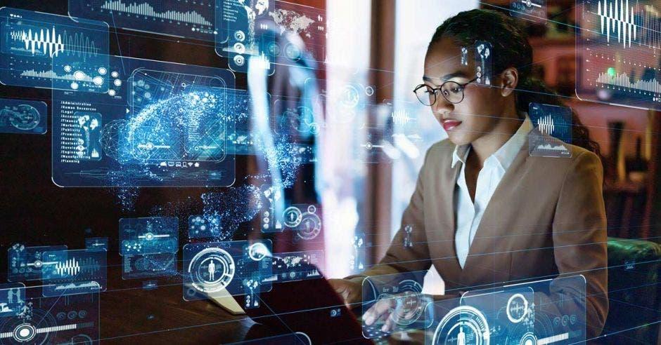 mujer con saco beige y lentes, frente a una computadora y diagramas de tecnología