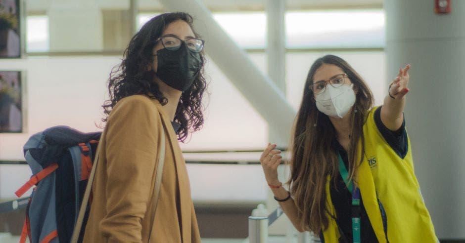 una mujer de chaleco amarillo da indicaciones a otra mujer de abrigo marrón en el pasillo de un aeropuerto