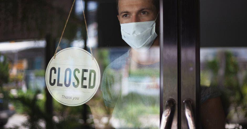 un hombre con mascarilla en la entrada de un local de comida. Letrero de cerrado en la entrada.