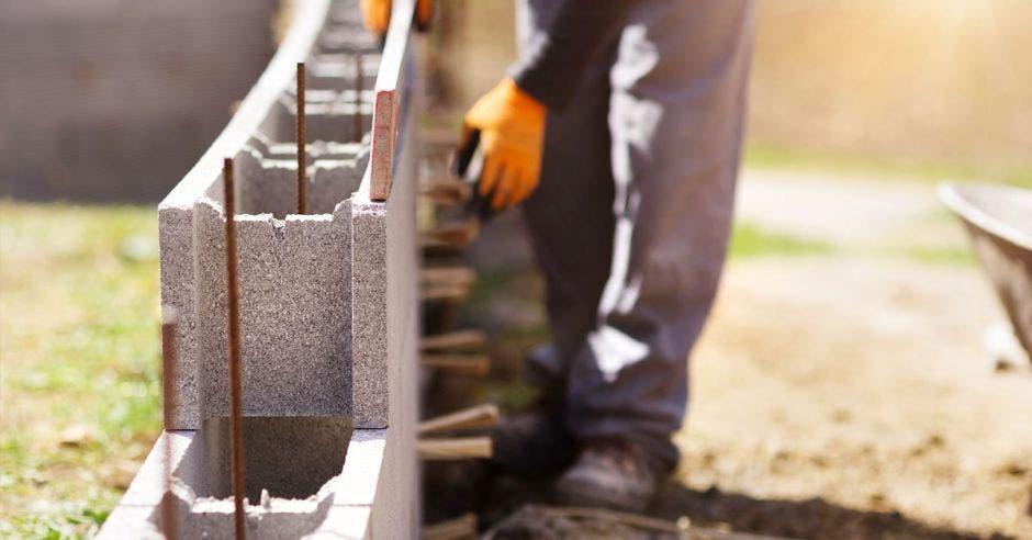 un hombre pone bloques de construcción en medio de varillas de acero