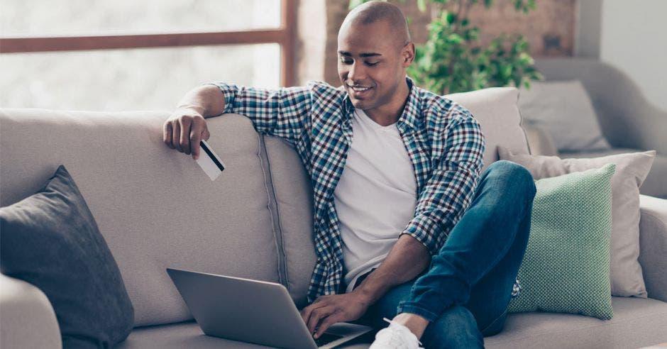 hombre joven sentado en sofá con tarjeta de crédito en la mano y laptop