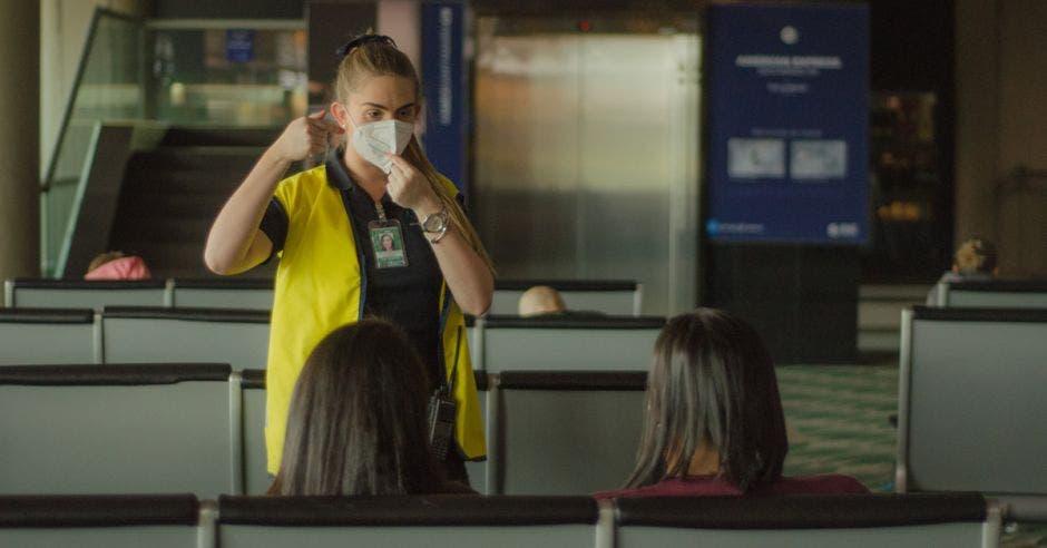 una mujer con mascarilla y chaleco amarillo le indica a dos persona una dirección