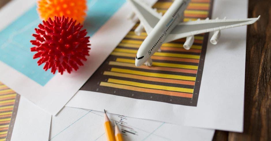 un avión sobre varios papeles y símbolos de coronavirus y lápices