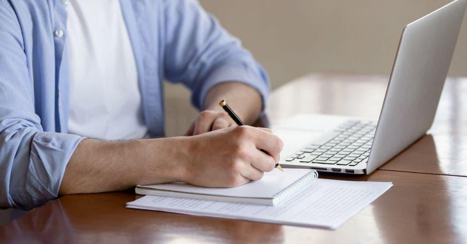 hombre tomando curso en línea y anotando en libreta