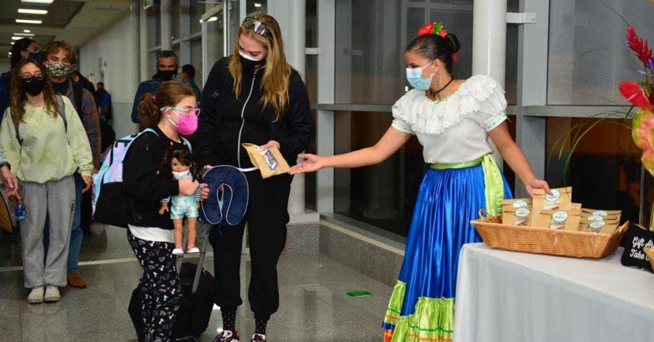 una mujer arribando al aeropuerto. La recibe una mujer de traje folclórico repartiendo panecillos.