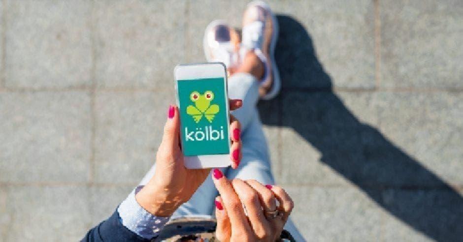 Mujer camina con un celular de kölbi