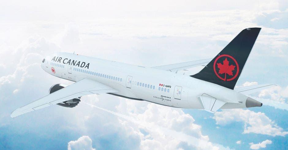 un avión blanco con un logo de hoja de maple rojo en su cola