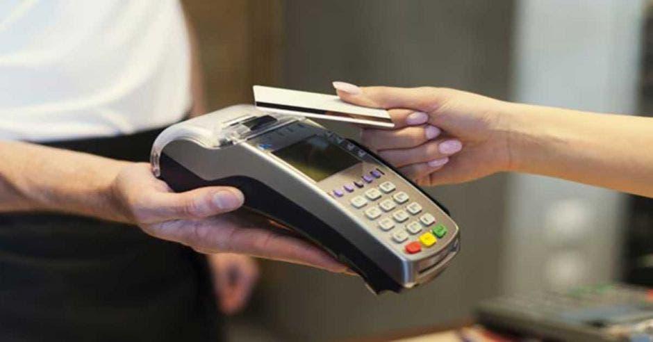 Persona acerca tarjeta a datáfono