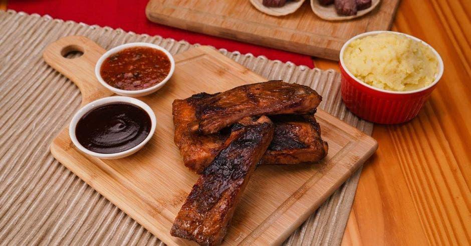 dos costillas cocinadas junto a salsas para acompañar
