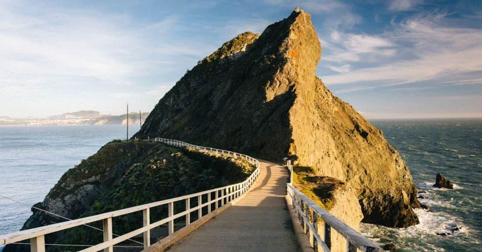 un sendero que conduce a una gran piedra en medio del mar