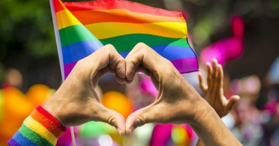 Persona haciendo corazón frente a bandera gay