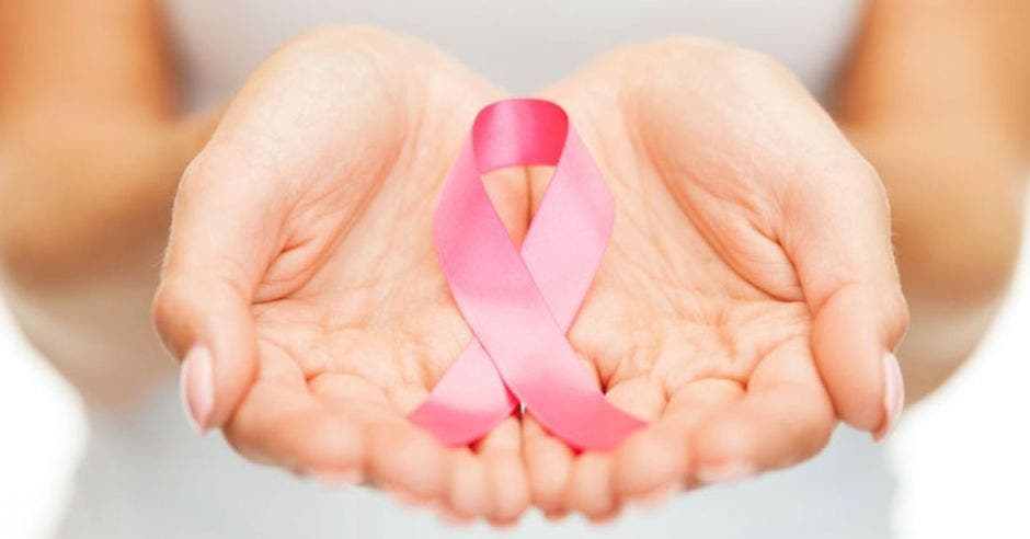 manos de mujer con lazo rosa