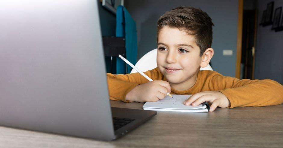 niño tomando clase virtual frente a laptop