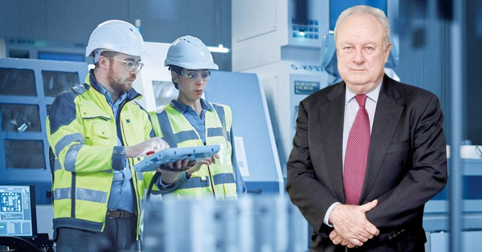 Hombre de traje y corbata frente a personas trabajando