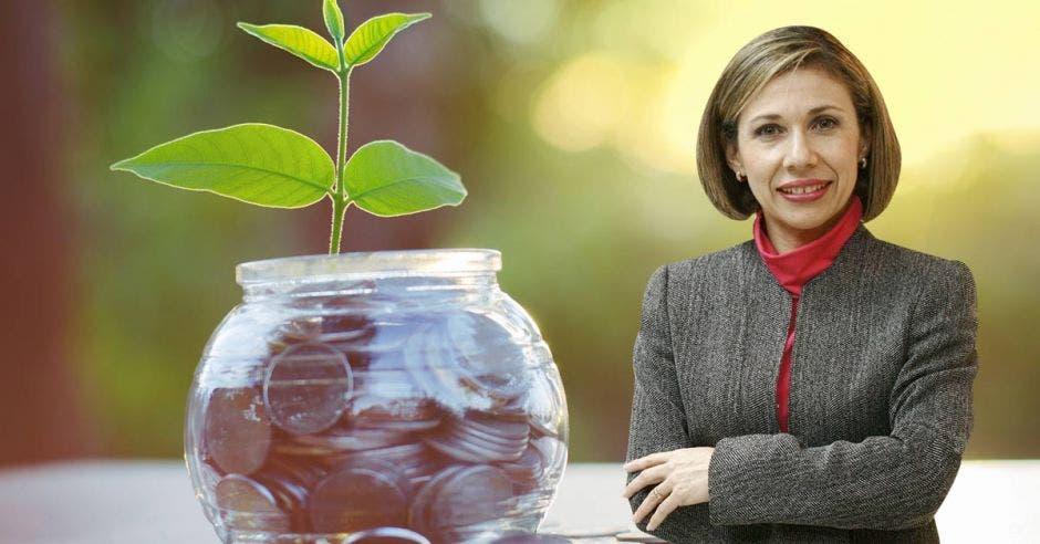 mujer de cabello corto, con sueter gris y blusa roja, cruzada de brazos, de fondo un tarro de vidrio con monedas y una plantita encima