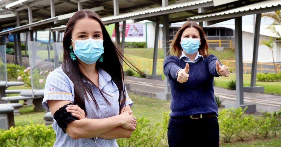 dos mujeres de camisas de azules mostrando el pulgar arriba