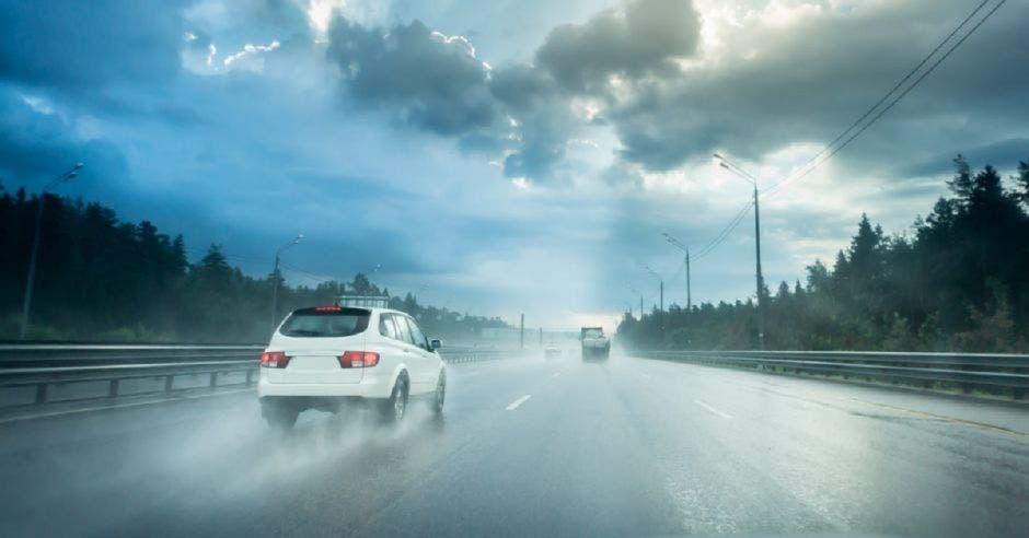 Carro conduciendo a alta velocidad en carretera mojada