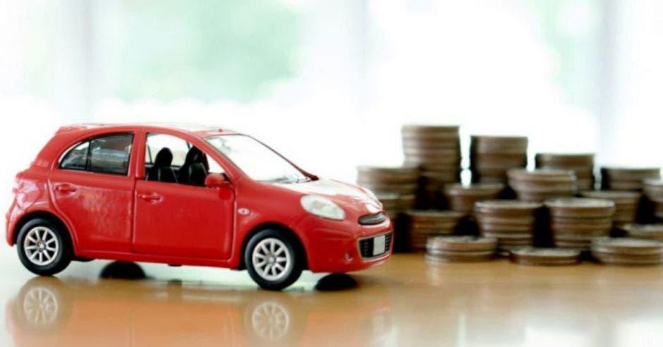 figura pequeña de carro rojo junto a monedas