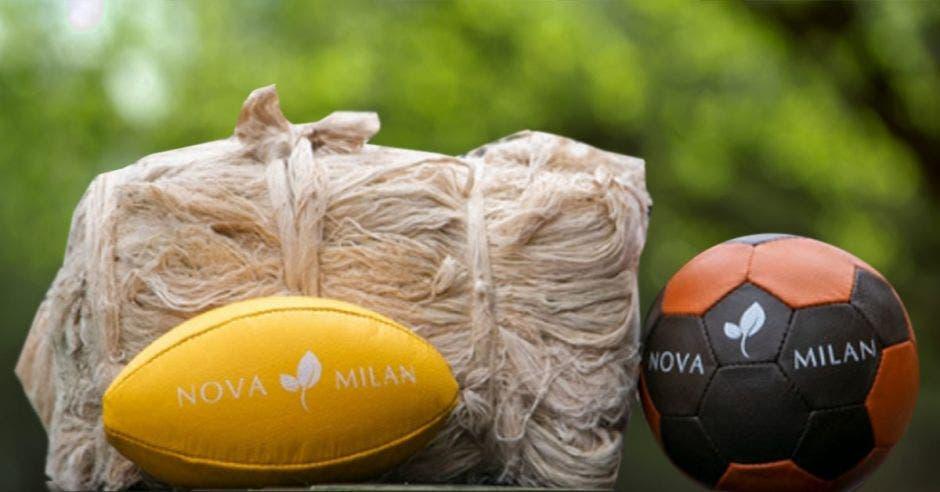 un balón de fútbol americano, un bolso tejido y una pelota de voleibol sobre una mesa