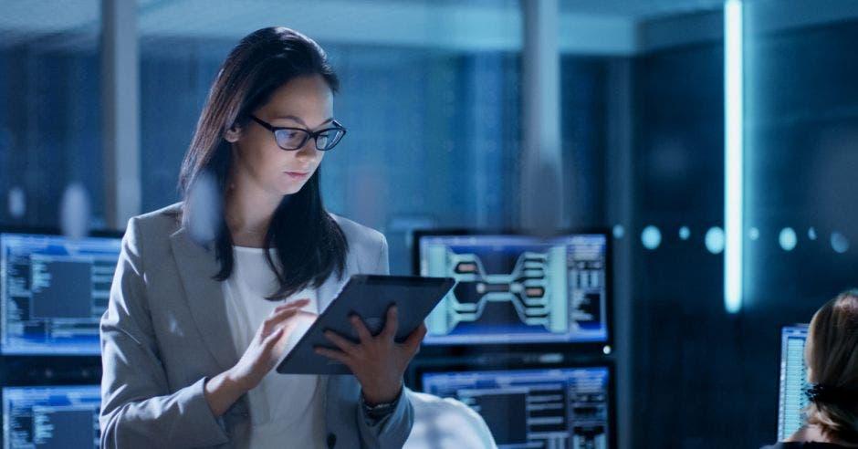 una mujer revisa una tablet en medio de un salón con varios gadgets tecnológicos