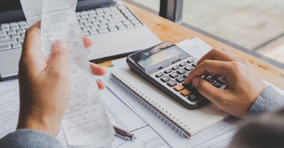 Mano de persona en calculadora y factura