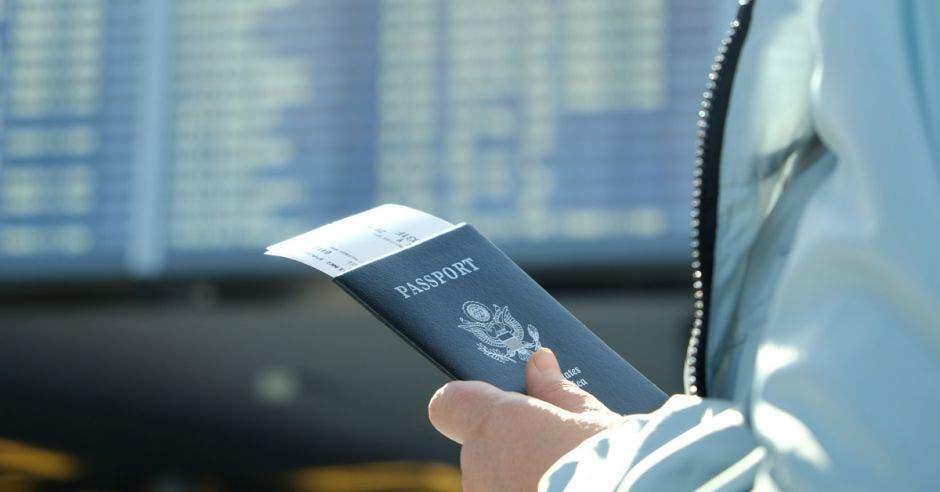 una persona sostiene un pasaporte de Estados Unidos en su mano