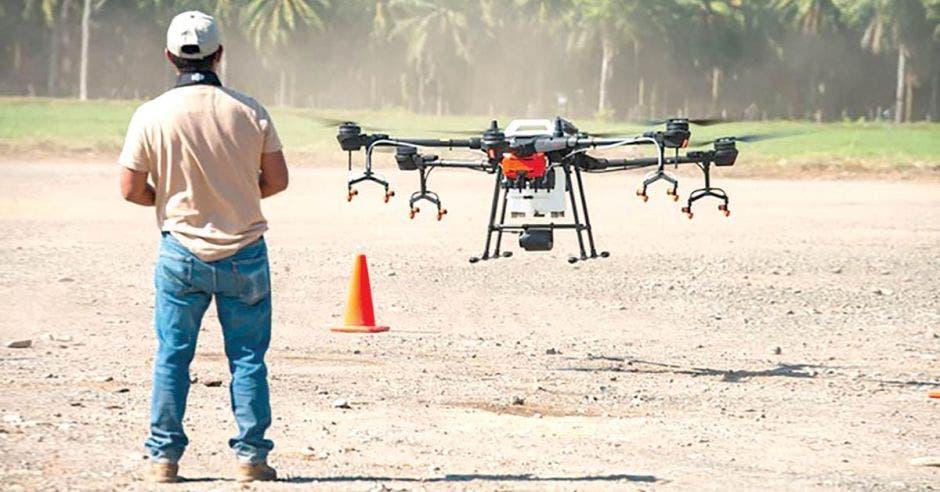 hombre de espaldas volando dron en campo