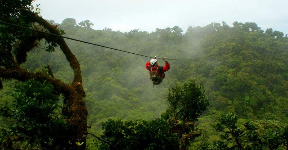 Un turista montando la tirolesa sobre un cañón de bosque nuboso profundo en Monteverde