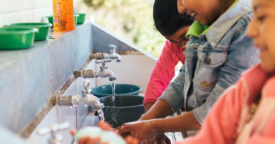 un grupo de niñas se lava las manos con agua y jabón