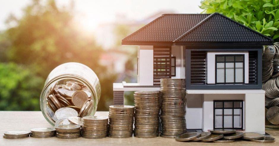 maqueta de casa con monedas a un lado