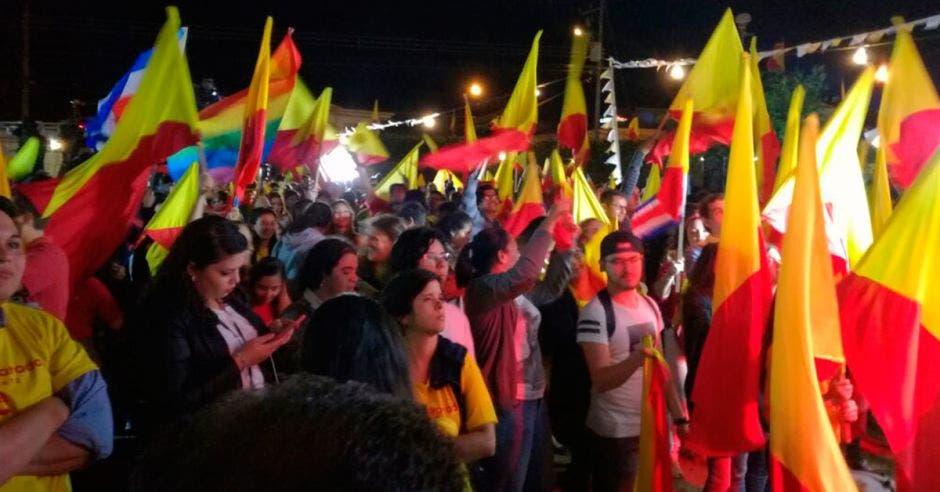 Adeptos del PAC bailan en su sede mientras esperan resultados. Banderas amarillas y rojas ondean en las calles.