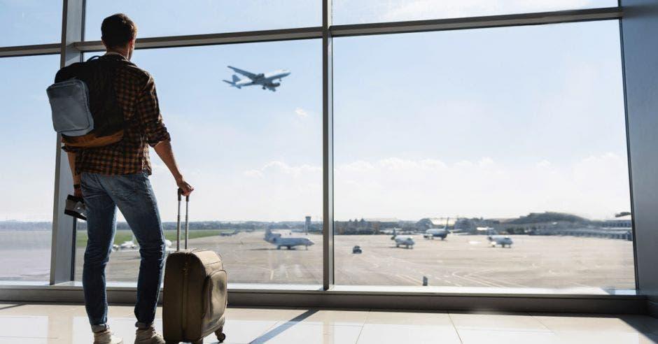 un hombre con equipaje en el lobby de un aeropuerto