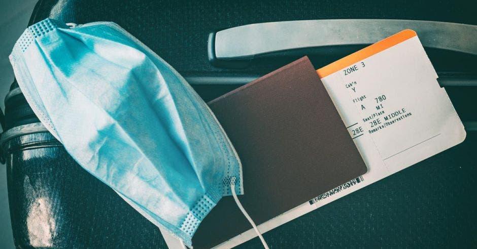 una mascarilla y un pasaporte sobre un maletín