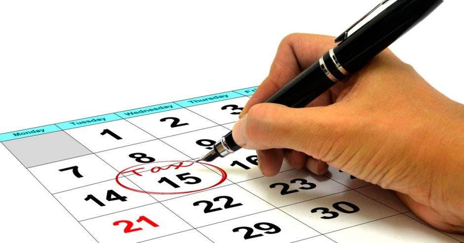 Persona con bolígrafo marca calendario