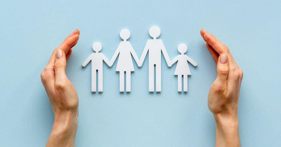 fondo azul claro, con figuras de papel de dos adultos y dos niños en medio de dos manos encorvadas