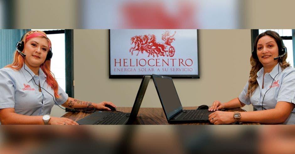 dos mujeres con camisa azul sentadas frente a laptop usando headsets
