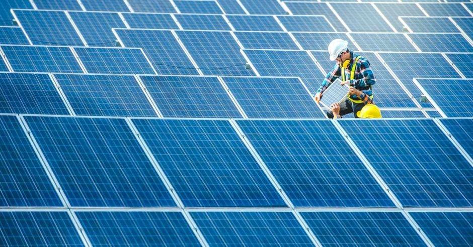 un hombre arregla paneles solares en el techo de un edificio