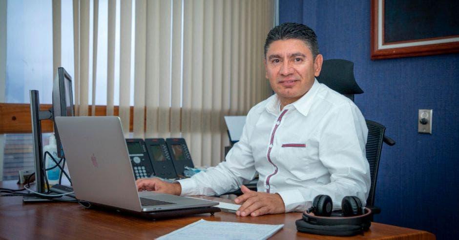 Hombre sentado en oficina frente a computadora