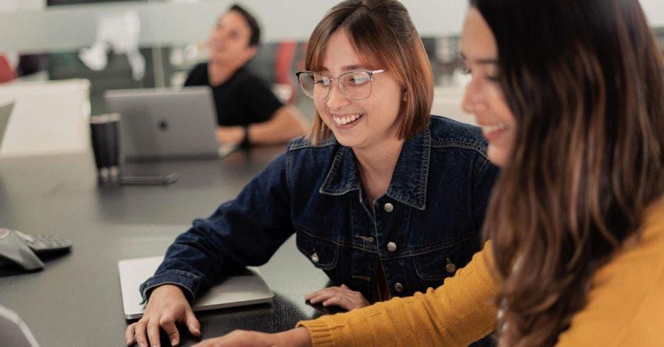 dos mujeres manipulan una computadora en un escritorio